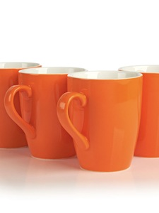 Porcelain mug set of four in citrusy orange.